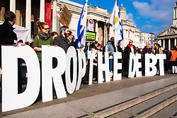 "London, February 15th 2015. Londoners demonstrate in solidarity with Greeks in their fight against the EU's insistance that they maintain their programme of austerity. PICTURED: Protesters hold up a large ""Drop The Debt"" sign."