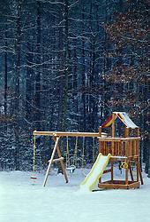 Winter snow scene childrens  backyard playground, swings, slide board , edge of forest. CONCEPT STOCK PHOTOS