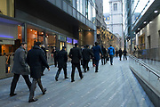 Workers in the City of London walk home past their offices in the evening after work, London, UK.