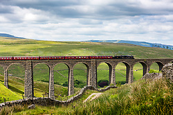 © Licensed to London News Pictures. 12/06/2018. Stonehouse UK. Locomotive 45690 Leander crosses over the Arten Gill viaduct in the Yorkshire Dales today. Arten Gill viaduct was built as part of the Settle & Carlisle Railway between 1870-1875 by Victorian engineer John Sydney Crossley & constructed using Dent Marble, it has eleven arches & spans 201 metres. Photo credit: Andrew McCaren/LNP