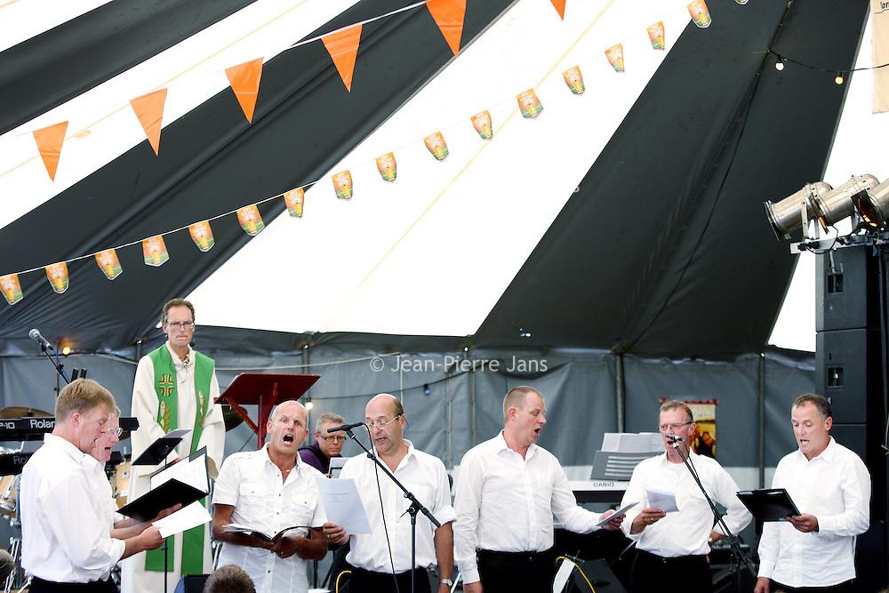 Nederland, Marken , 23 juni 2010..Marken (plaatselijk: Mereke) is een voormalig eiland in de Zuiderzee, tegenwoordig Markermeer dat sinds 1957 via een dijk met het vasteland verbonden is. Het behoort tot de gemeente Waterland in de provincie Noord-Holland..Marken vormt in wezen één leef- en woonplaats, maar is opgedeeld in diverse buurtschappen. Oorspronkelijk lagen die ook echt los van elkaar. Tegenwoordig liggen sommige buurten aan elkaar, zoals Havenbuurt, Kerkbuurt en Kets..Op de foto de Havenfeestenkerkdienst geleid door ds. Visser met het Marker Mannenkoor..Marken is a former island in the Zuiderzee, now Markermeer  and connected through a dike to the mainland since 1957. The natives are still in costume, and that attracts tourists as are the green wooden houses..The church in a marquee service with a men's choir during the Markens' Port Festival.