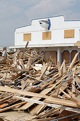 Stock photo of storm debris piled in front of a damaged storefront