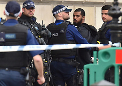 Armed police detaining a man carrying a bag of knives in Whitehall in London.