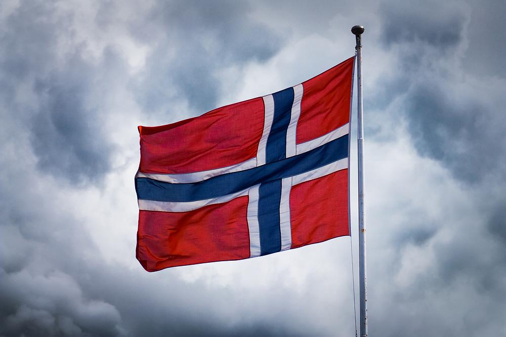 Norges flagg mot himmel med skyer.