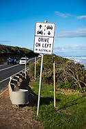 A sign on the Great Ocean Road in Victoria, intended for visitors to Australia who are accustomed to driving on the right-hand side of the road, reminds drivers to drive on the left in Australia.