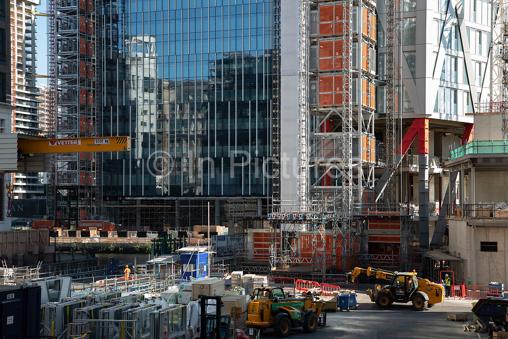 Construction site of new 60 storey residential tower block Newfoundland at Canary Wharf financial district in London, England, United Kingdom. Newfoundland is a 60-storey residential building which will be situated on the western side of the Canary Wharf Estate and bound by Westferry Road to the west, Middle Dock to the east, and Bank Street to the south. The slim diamond shape of the tower is determined by the narrow footprint of the site. The dia-grid structural system expressed on the facade of the building supports and braces the structure.