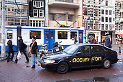 Saab car with graffiti parked at the Occupy Amsterdam demonstration outside the Amsterdam Stock Exchange at Beursplein, Amsterdam, the Netherlands. This is one of many 'occupy' protests following the Occupy Wall Street protests in New York, against economic inequality. October 19th 2011.