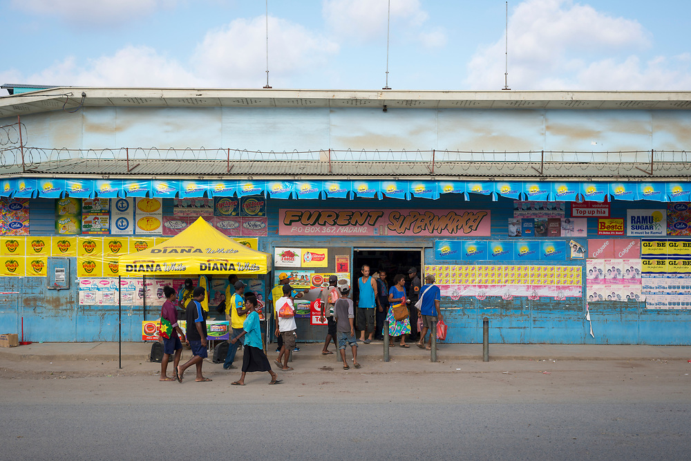 A security guard watches people enter and exit a supermarket in Madang, Papua New Guinea. Crime is a major issue in the country, and many businesses have security guards, and sometimes razor wire, on the premises. (August 7, 2017)
