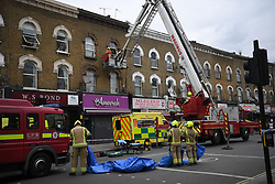 © Licensed to London News Pictures. 01/04/2020. London, UK. A patient is lowered to the ground at an incident involving all emergency services where a suspected COVID-19 case was isolatedand removed from their home. Uxbridge Road in Shepherd's Bush was closed for an hour as ambulance, fire brigade and police attended, extracting the patient by crane from a three story apartment building in West London. PPE (personal protective equipment) was in evidence, with the fire brigade using full facerespirators normally reserved for firefighting. A police officercommented the Metropolitan police force are issued only with rubber gloves. Ambulance workers decontaminated the scene and reusable equipment before moving on.  Photo credit: Guilhem Baker/LNP
