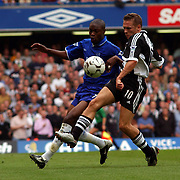 Newcastle United's Craig Bellamy holds off Chelsea's William Gallas