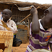 Children drumming at the Gambela Sunday School. These refugees from Ethiopia are now part of the Christian minority among Dadaab's largely Muslim population. North Eastern Province, Kenya.