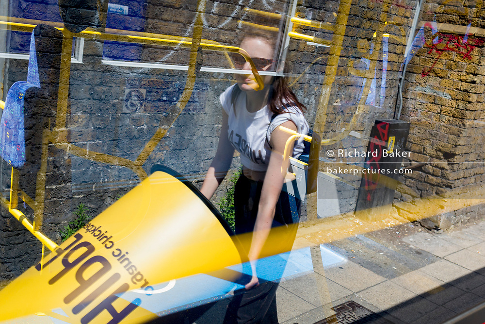 With the reflections of a parked London bus, a woman pushes marketing props along a side street in Waterloo, SE1, on 16th July 2019, in London, England.