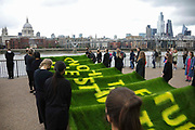 Art work by Ackroyd & Harvey made in grass with words by Ben Okri is set to float on the rising tide on the Thames on the 25th of June 2021, Central London, United Kingdom. The message is a call for action to save the planet from climate change catastrophe. The art work was moved by activists and laid onto a raft on the Thames as the tide was rising. The event marks the launch of XR Writers Rebel's Paint the Land project, which teams acclaimed writers and artists to create landscape graffitos drawing attention to the climate and ecological emergency. The Speakers at the event included the artist Ackroyd & Harvey, writer Ben Okri, Kelly Hill and Simon Bramwell, co-founder of Extinction Rebellion.  The event finished with a song by Damon Albarn and Mirabella Okra and the Capital Choir.