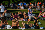 Large groups of people (against both current and future guidance) enjoy the sun on Clapham Common after the Government eased restrictions and allowed people to meet - Lambeth Council have replaced signs to say stay alert and to allow people sit on benches. The eased 'lockdown' continues for the Coronavirus (Covid 19) outbreak in London.