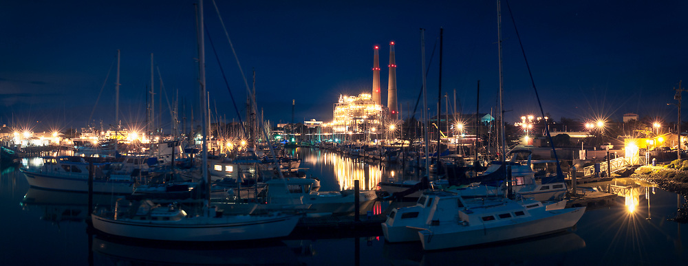 The Moss Landing harbor and power plant are seen on a moonlit night.
