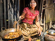 30 OCTOBER 2015 - TWANTE, MYANMAR: A woman cooks lunch in her home in the potters' village in Twante, (also spelled Twantay) Myanmar. Twante, about 20 miles from Yangon, is best known for its traditional pottery. The pottery makers are struggling to keep workers in their sheds though. As Myanmar opens up to outside investments and its economy expands, young people are moving to Yangon to take jobs in the better paying tourist industry or in the factories that are springing up around Yangon.     PHOTO BY JACK KURTZ
