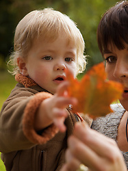 Close up of a woman with a child in her arms holding a leaf