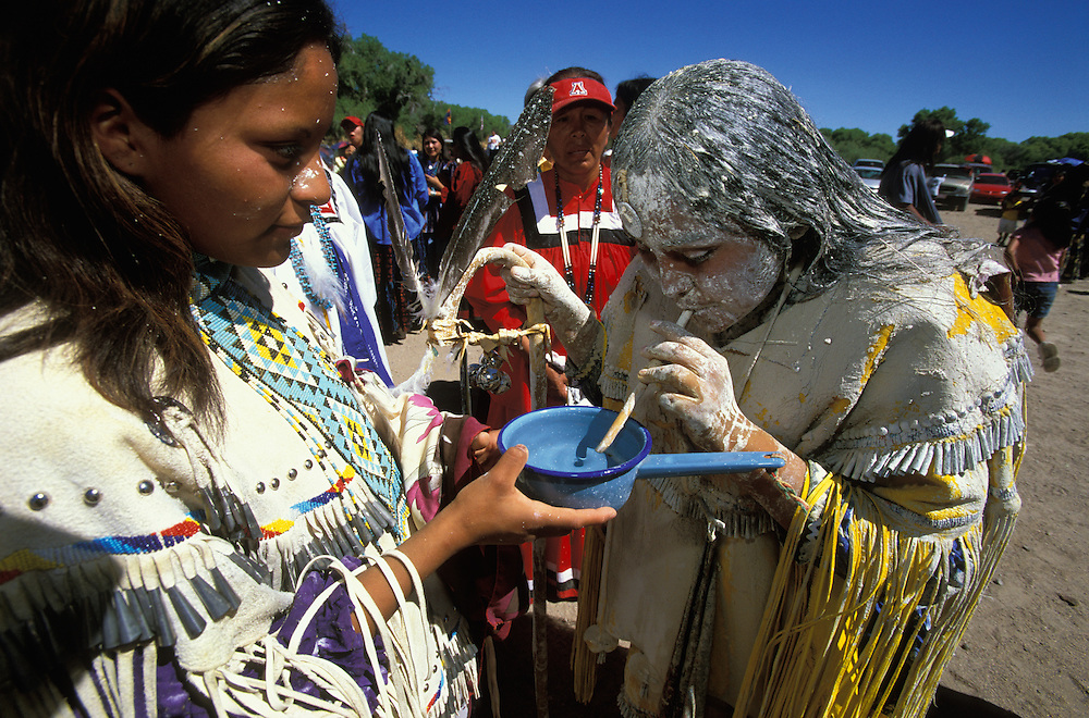 An Apache girl uses a straw to drink water from a dipper during her Sunrise Dance, a first menstruation rite, on the San Carlos Apache Indian Reservation in Arizona, USA. The girl is covered in sacred white clay and corn meal that has been applied both as a blessing and as an enactment of certain parts of the Apache creation myth. During the rites the girl 'becomes' Changing Woman, a mythical female figure, and comes into possession of her healing powers. The rites are also supposed to prepare the girl for adulthood and to give her a long and healthy life without material wants.