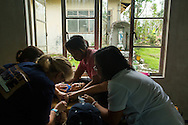 Project HOPE volunteers work to insert an IV into a child's arm at Tapaz District Hospital on Panay Island, Philippines.