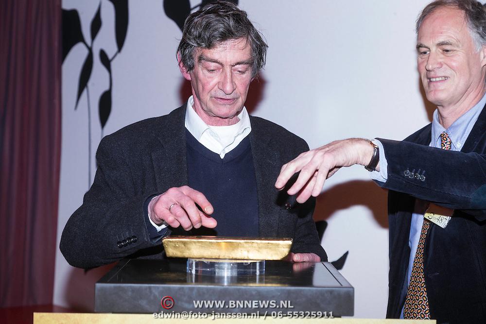 NLD/Amsterdam/20140220 - Boekpresentatie Fout Geld in De Nederlandse Bank Thomas Ross probeert een baar goud op te tillen op verzoek van Roel Janssen