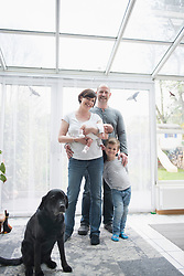 Portrait of happy family with pet dog, Munich, Bavaria, Germany