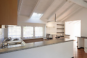 Front view of vintage kitchen with wooden furniture. Three small windows