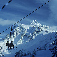 Skiers ride a chairlift at Washington's Mount Baker Ski Area, with Mount Shuksan rising in the background