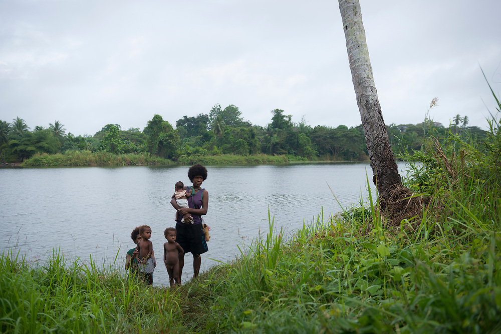 Two women and three children stand on the banks of an oxbow lake near the village of Timbapmining, located on the Ramu River in Madang Province, Papua New Guinea (July 2017)
