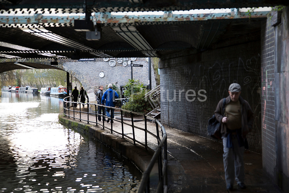 People walking along the towpath under bridges arching over Regents Canal at Camden Town, London, UK.