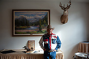 Posed portrait of Charlie Lyons, of St. Ignatius, Montana, a retired rodeo clown and Cowboy Hall of Famer, in the lobby standing next to his award statue at the New Code of the West Conference held at the Grouse Mountain Lodge in Whitefish, Montana, USA, October 13, 2018.