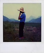Polaroid SX 70 portrait of a chinese farmer in his field. He's smoking while observing countryside land surrounding him. Guangxi province, China, Asia.