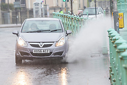 © Licensed to London News Pictures. 19/01/2019. Brighton, UK. Cars drive through deep puddles of water on the side of the road as Brighton and Hove is hit with rain and cold weather. Photo credit: Hugo Michiels/LNP
