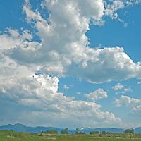 Cumulus thunderheads drift over Montana's Gallatin, near Bozeman.  Behind is the Gallatin Range.