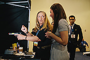 Ann Tumolo, right of center, is taught how to properly hold an electronic gun at the NRA booth during the final day of the Conservative Political Action Conference (CPAC) at the Gaylord National Resort & Convention Center in National Harbor, Md.