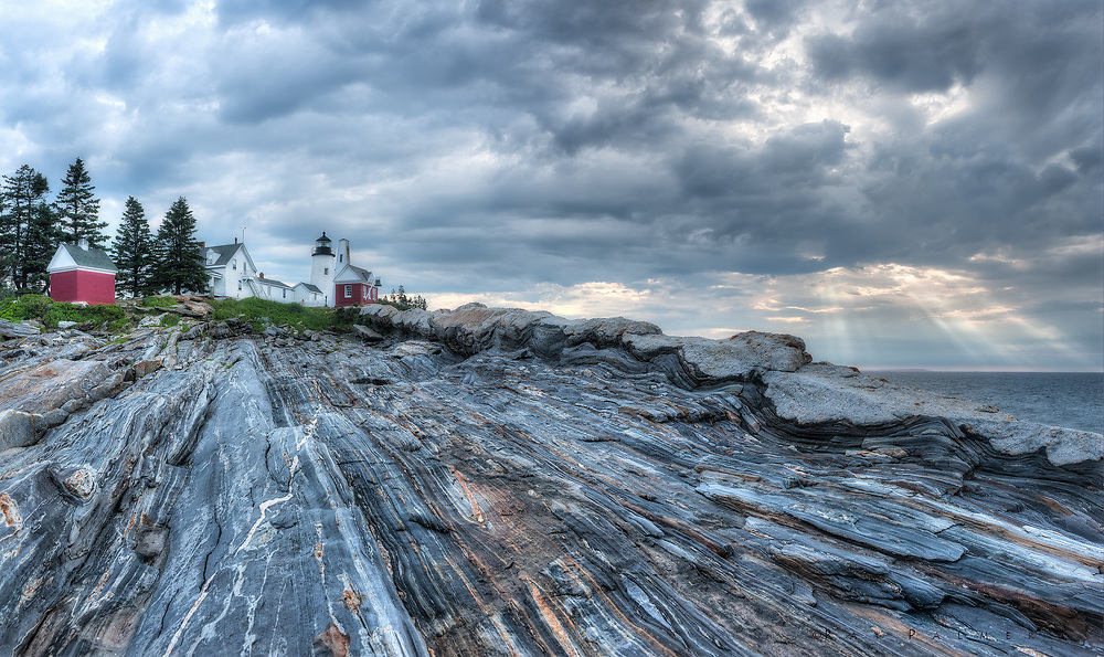Pemaquid Point, Maine.<br /> At the end of Bristol Road is a finger of land, with a lighthouse and watcher's residence perched on the last soil before bedrock.  The shelf slopes down into the Atlantic, sedimented layers flipped and folded and shot through with igneous white intrusions.  It was down on this ramp that I scrambled with an eye towards capture, the ocean still quiet under a gathering sky.  On the polished and deceiving rock, I fell with no warning, smashing a polarizer and embarrassing myself in my stupidity.  I chided myself for going down yet another dead end, hoping for something better than the forecast I could see when I set out.  I have been down so many of these cul-de-sacs, you would think I would know better, chasing things in the name of love, or for the love of discovery.  The lines mix I gues, the objectives if there are any, are not thought through.  This is what I get, I think, for not trusting my inner voice, for following my heart.  I dust myself off, resolving not to let promise lead to more impasses, knowing another level down that I probably won't change.  In the distance, I am mocked by a break in the clouds.