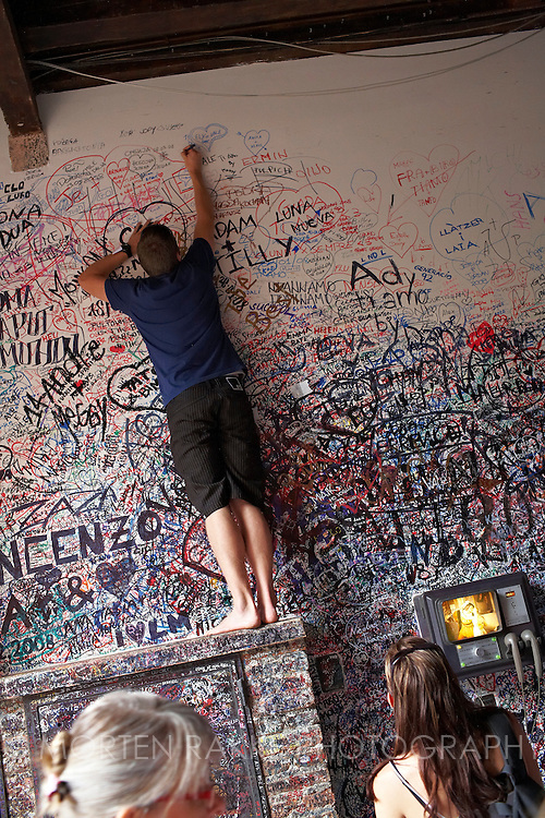 A man writes a message on the wall at Juliets place, Via Capello 23, Verona, Italy. The famous place from the story about Romeo and Juliet, by William Shakespeare.