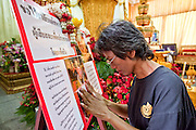 """18 MAY 2010 - BANGKOK, THAILAND: Women pray at pictures of Seh Daeng at Wat Somanus Tuesday, May 18. The body of Royal Thai Army Maj. General Khattiya """"Seh Daeng"""" Sawasdipol, is lying in repose at Wat Somanus in Bangkok, Thailand. Seh Daeng was widely thought to be the military leader of the Red Shirts. He was credited with ending Thailand's communist insurgency in the 1970's and 80's which made him a folk hero among many people in northeast Thailand. He was shot by an unidentified sniper on May 13 and died on May 17. The anti government Red Shirts have announced a three day mourning period the Seh Daeng.  PHOTO BY JACK KURTZ"""
