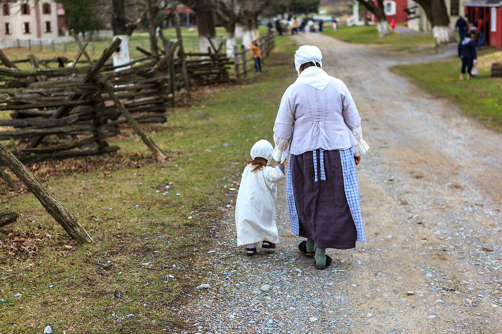 Lancaster, PA, USA / March 13, 2011: A young child and her mother walk on a country road at the Landis Valley Farm Museum.
