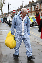 © Licensed to London News Pictures. 09/04/2019. London, UK. A crime scene investigator with a bag of belongings on Church Road, Manor Park, East London where a man in his 20s was shot and stabbed to death on Monday 8 April 2019. Police were called around 9.30pm and the man was was found with knife and gunshot wounds. The victim was pronounced dead at the scene. Photo credit: Dinendra Haria/LNP