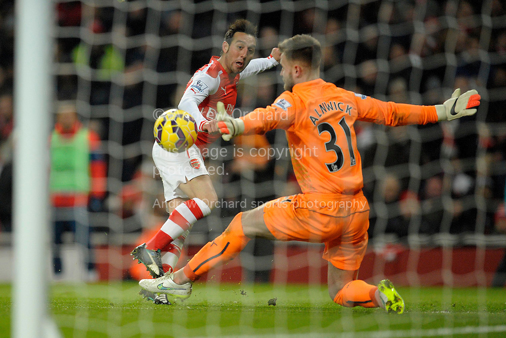 Santi Cazorla of Arsenal scores his teams second goal of the game to make it 2-0. Barclays Premier league match, Arsenal v Newcastle Utd at the Emirates Stadium in London on Saturday 13th December 2014.<br /> pic by John Patrick Fletcher, Andrew Orchard sports photography.