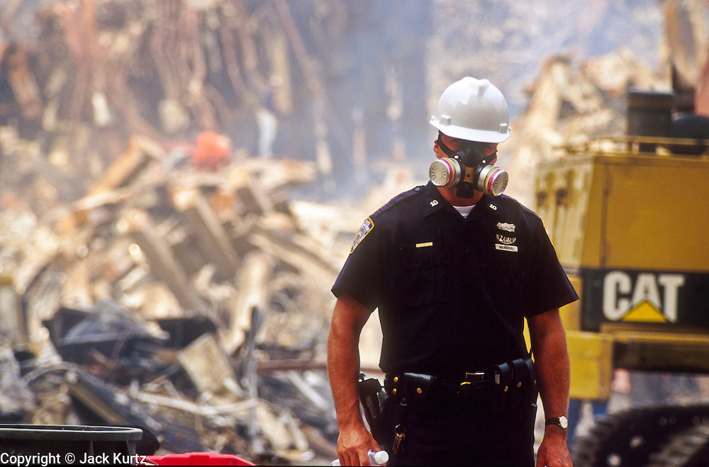 """NEW YORK, NY: A New York police officer wearing a breathing filter stands guard at """"Ground Zero"""" of the World Trade Center complex after the WTC terrorist attack, Sept. 22, 2001. Almost 3,000 people were killed when terrorists crashed hijacked passenger jets into the twin towers. PHOTO BY JACK KURTZ"""