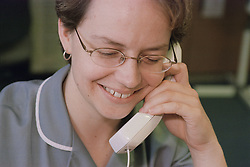 Midwife at work station using telephone smiling,