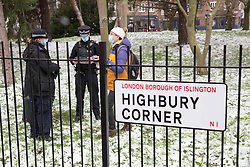 © Licensed to London News Pictures.09/02/2021, London,UK. Police speak to a protester while bailiffs act under instructions from Islington Council to evict the Highbury Corner Tree Protection Camp in north London. The camp is not strictly part of campaign to stop HS2. Bailiffs entered the camp at 5am and discovered the tunnel underneath the square. It is planned to cut trees for the new six-story building. Photo credit: Marcin Nowak/LNP