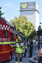 © Licensed to London News Pictures. 23/08/2019. London, UK.  Firefighters attending scene with Grenfell Tower in background. A fire broke out on the 12th floor of a tower block very close to the devastating inferno that destroyed Grenfell Tower killing 72 people two years ago. Ten engines and 70 firefighters brought the blaze under control which gutted the apartment and spread externally along satellite cables. Residents of Markland House self evacuated and commented that no fire alarms were heard in the building.  Photo credit: Guilhem Baker/LNP