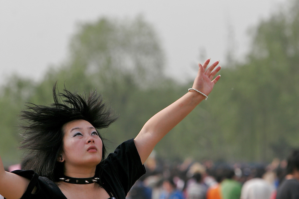 A girl jumps after releasing a kite in an open area at Midi Festival in Beijing China 2007.  Midi is an alternative music festival held in northern Beijing catering to a small group of music listeners.  The festival lasts 4 days and gives performances from Chinese and international bands.