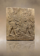 Photo of Hittite sculpted Orthostats panel of Long Wall Limestone, Karkamıs, (Kargamıs), Carchemish (Karkemish), 900-700 B.C. Soldiers. Anatolian Civilisations Museum, Ankara, Turkey<br /> <br /> Figure of two helmeted warriors. They have their shield in their back and their spear in their hand. The prisoner in their front is depicted small. A human head is depicted in the left hand of the warrior in the front. The warrior at the rear holds the prisoners sitting on his lap from his hair. Below this figure, which was described small, lies yet another small human figure. <br /> <br /> On a brown art background. .<br />  <br /> If you prefer to buy from our ALAMY STOCK LIBRARY page at https://www.alamy.com/portfolio/paul-williams-funkystock/hittite-art-antiquities.html  - Type  Karkamıs in LOWER SEARCH WITHIN GALLERY box. Refine search by adding background colour, place, museum etc.<br /> <br /> Visit our HITTITE PHOTO COLLECTIONS for more photos to download or buy as wall art prints https://funkystock.photoshelter.com/gallery-collection/The-Hittites-Art-Artefacts-Antiquities-Historic-Sites-Pictures-Images-of/C0000NUBSMhSc3Oo