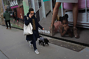 A man walks his dog past a large billboard, part of a series of portraits by photographer Lucy Alex Mac, that show pregnant women at West Smithfield, in the former Smithfield meat market that is awaiting future redevelopment, on 20th November 2019, at Smithfield in the City of London, England. As part of the Museum of Londons plans to move into Smithfields General Market Building, this photography show celebrates pregnant residents of Waltham Forest. The cost of the move is estimated to be in the region of £70 million and, if funding can be achieved, would be complete by 2021. There has been a market on this location since the Bartholomew Fair was established in 1133 by Augustinian friars.