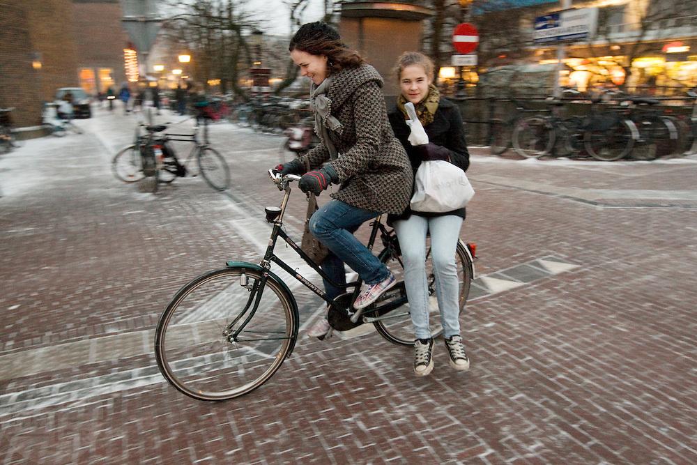 Twee meisjes fietsen door Utrecht, een meisje zit achterop