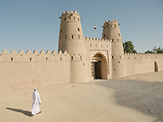 A man walks towards the entrance of the Al Jahili Fort, one of the UAE's most historic buildings. It was erected in 1891 to defend the city and protect precious palm groves.