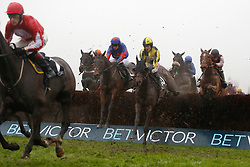 Splash Of Ginge and Tom Bellamy (red star on cap) clear an early fence before going on to win The BetVictor Gold Cup Handicap Steeple Chase Race run during day two of the November Meeting at Cheltenham Racecourse.